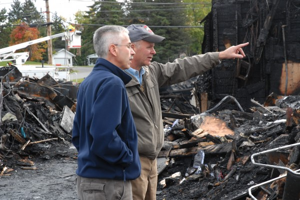 Carl Theriault (right), owner of Valley Auto, discusses the removal of waste oil from tanks with Burt Levesque of Daigle Oil Co. Theriault's business was destroyed in a fast-moving fire Wednesday, but thanks to a communitywide effort, most of his inventory, computers and files were saved. Valley Auto has reopened on a limited basis at Lonesome Pine Ski Lodge in Fort Kent.