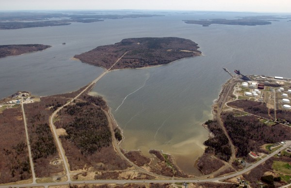 A causeway bends to the right, connecting the mainland to 941-acre Sears Island in Searsport on Penobscot Bay. Mack Point with its oil and gasoline tank farm is visible to the right, and U.S. Route 1 is visible at the bottom of the photo, taken in 2004.