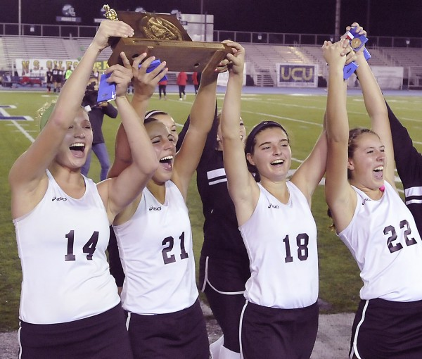 Skowhegan High School field hockey team seniors Adrianna Martineau (14), Makaela Michonski (21), Sarah Finnemore (18) and Erica Blake (22) celebrate with the trophy after defeating the Scarborough High School team 3-0 in the State Class A Championship game in Orono, Maine, Saturday, Oct. 27, 2012.