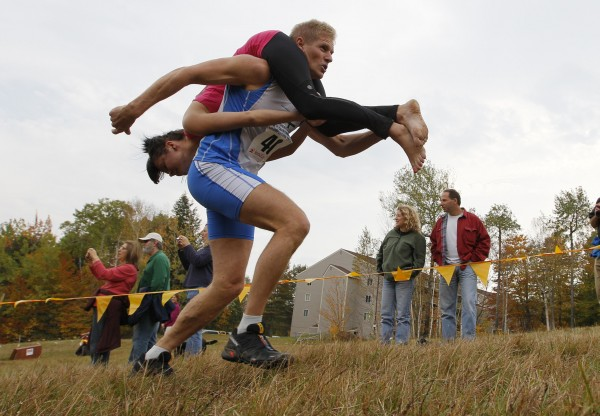 Taisto Miettinen carries Kristiina Haapanen, both from Finland, en route to winning the 2012 North American Wife Carrying Championship, Saturday, Oct. 6, 2012, at the Sunday River Ski Resort in Newry, Maine.