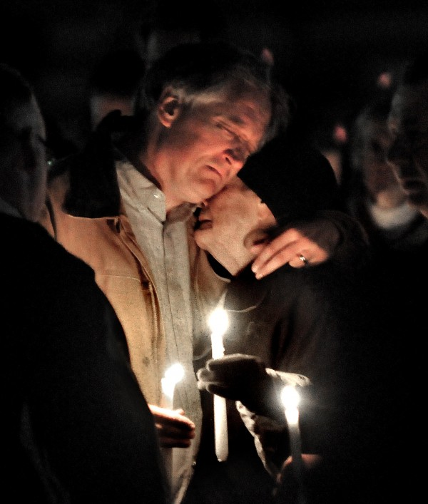 Robert Marriott, father of Lizzi Marriott, is consoled during an emotional candlelight vigil on Saturday night, Oct. 13, 2012, at the Bay State Commons, for his daughter, Elizabeth &quotLizzi&quot Marriott of Westboro, a University of New Hampshire student, who disappeared earlier in the week. Marriott is believed to be dead, and a man has been charged with second-degree murder.