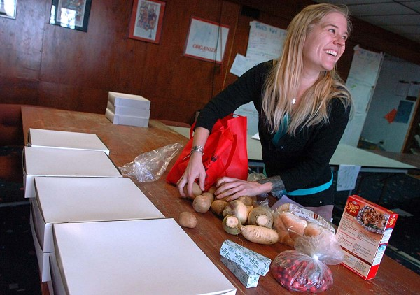 Willow Cortes-Eklund, Solidarity Harvest Coordinator, displays a selection of food provided to local families by Food AND Medicine and the Eastern Maine Labor Council in November 2011, at the Food AND Medicine headquarters in Brewer.