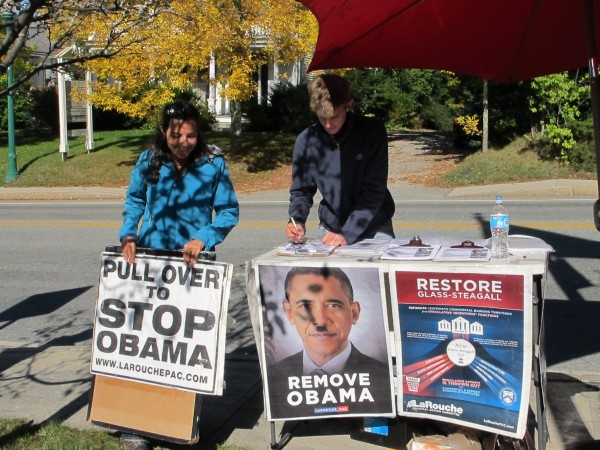 Two activists from Larouche PAC handed out pamphlets to passersby in Ellsworth on Tuesday, Oct. 2, 2012. The duo drew attention with posters depicting Obama with a Hitler mustache.
