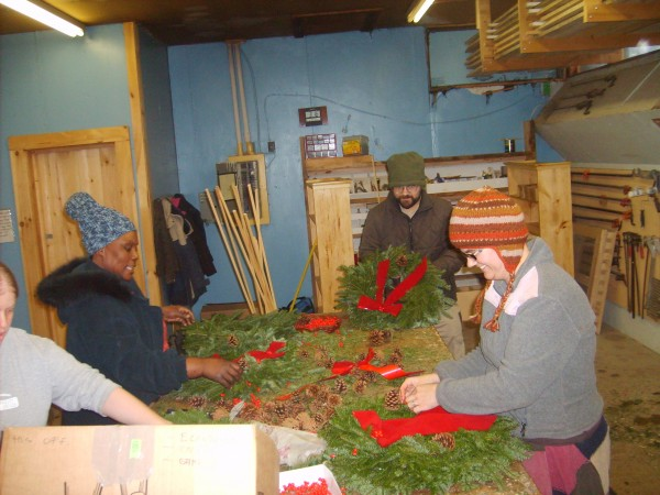 Mark Levesque (holding wreath) Karen Botta (right) and Gerald Botta (foreground) who work at H.O.M.E. Co-op, and a unidentified volunteer, add decorations to finished wreaths at H.O.M.E. in Orland.