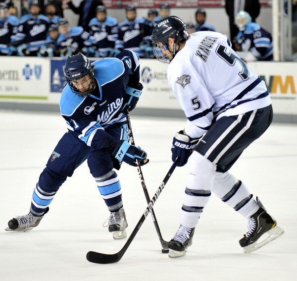 Maine forward Kyle Beattie (21) tries to get around New Hampshire defenseman Eric Knodel (5) during a game last season. Maine will be looking for more point production this season from Beattie.