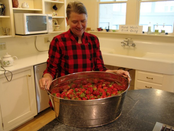Cheryl Wixson enjoys some Maine strawberries in her kitchen earlier this year.
