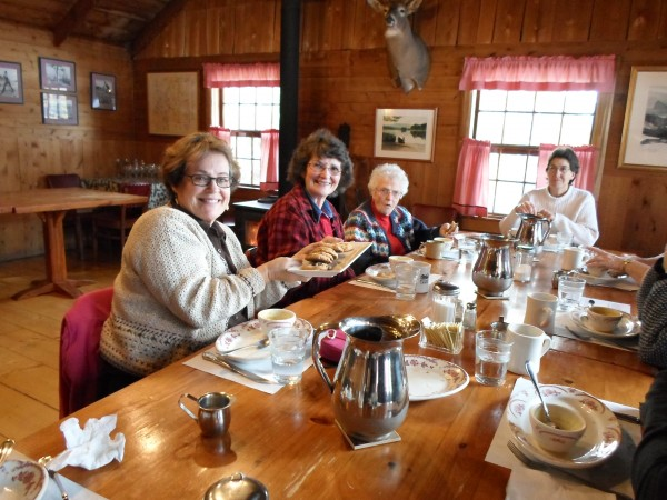 Shirley Cote (from left) and Wendy Bossie pass the chocolate chip cookies toward Jane McEwen and Carol Castle after a gourmet lunch on Oct. 16 at Bradford Camps on Munsungun Lake.