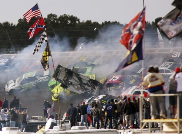 Tony Stewart (14) flips over as Clint Bowyer (15), Regan Smith (78), Jeff Burton (31), Jimmie Johnson (48), Casey Mears (13), Aric Almirola (43), Dale Earnhardt Jr., (88) and Sam Hornish Jr. (22) crash around him during the NASCAR Sprint Cup Series auto race at Talladega Superspeedway in Talladega, Ala., Sunday, Oct. 7, 2012.