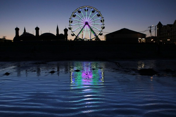 The colorful lights of Palace Playland's new Ferris wheel reflect in the surf at Old Orchard Beach.
