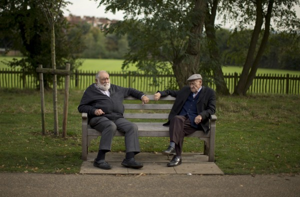 Two men sit on a bench on the periphery of the Hampstead Heath Heritage Festival, which is a celebration of old England on Hampstead Heath in London, Sunday, Oct. 7, 2012.