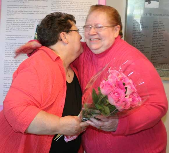 Rita Daigle (left) of New Canada, hugs her sister Rosa Michaud of Presque Isle after presenting her with pink roses at an Oct. 3 ceremony during which Michaud was announced as the first honoree to have her profile featured in the County Cancer Hall of Courage. Michaud is a breast cancer survivor. The hall is located at the A.R. Gould Memorial Hospital in Presque Isle in the corridor that leads to The Aroostook Medical Center''s Aroostook Cancer Care clinic.