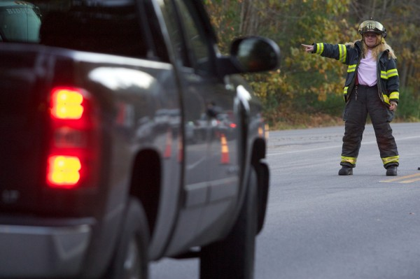 Goodwin's Mills firefighter Stacey Taylor directs traffic on Route 35 about a half mile from the scene of a reported shooting and fire in Dayton Tuesday, Oct. 16, 2012.