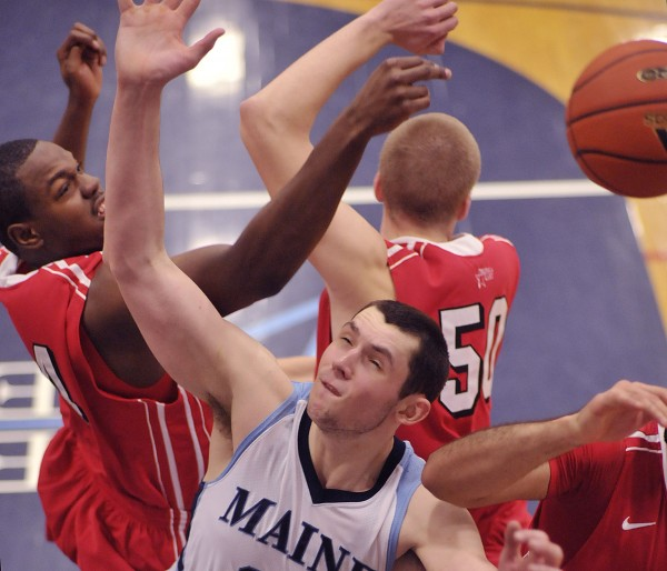 Alasdair Fraser of the University of Maine tries to control an offensive rebound against Corban Wroe (4) of Hartford during a basketball game last January in Orono. The junior forward on Tuesday was named to the Preseason All-America East Team.
