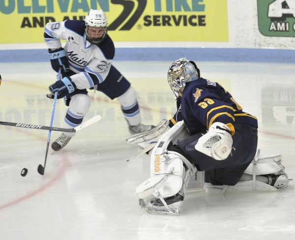 University of Maine winger Connor Leen (29) tries to stuff the puck around Quinnipiac goalie Eric Hartzell in the third period of their NCAA college hockey game Saturday in Orono. Quinnipiac won 2-1.