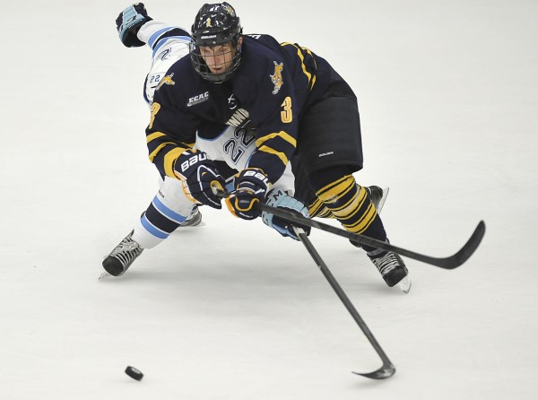 Quinnipiac defenseman Zach Davies (3) smothers a rushing Stu Higgins (22) of the University of Maine in the first period of Saturday's NCAA college hockey game in Orono.