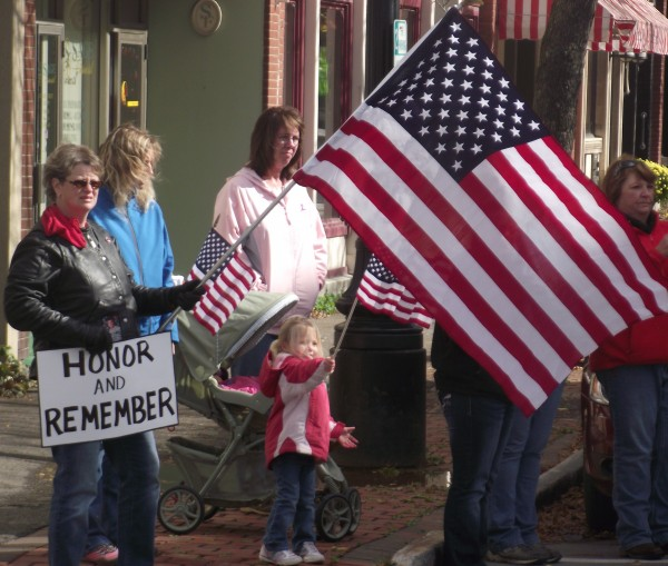 Clutching flags and homemade signs, residents started gathering in downtown Houlton a half hour early on Monday, Oct. 8, 2012, to greet the motorcade following the hearse that returned Sgt. 1st Class Aaron Henderson, a. U.S. Army Special Forces soldier, to Houlton. Henderson died in Afghanistan on Oct. 2 after being severely injured in an improvised explosive device attack on Sept. 30.