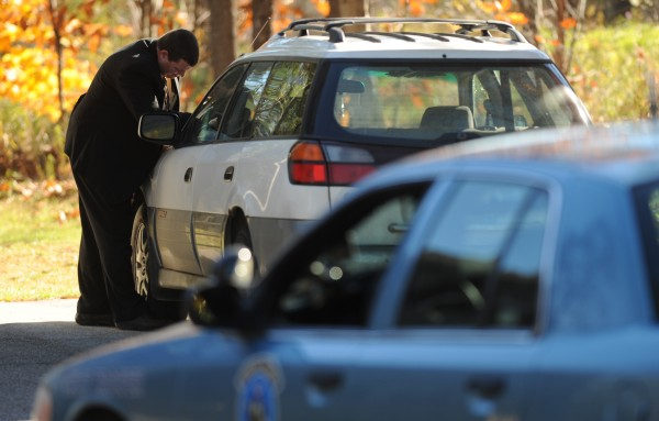 Maine State Police detective Brian Strout inspects a Subaru on Thursday, Oct. 25, 2012 at 69 New Boston Road in Hermon that matches the description of a car that dragged a person on Ohio Street earlier in Thursday.