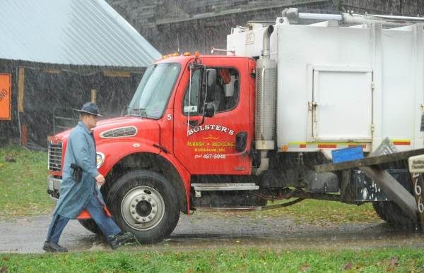 Maine State Police Trooper Christopher Cookson walks past a garbage truck owned by Bolster's of Burnham while investigating reports that the driver was shot at by a resident of a farm on Bowden Road in Corinna on Tuesday, Oct. 30, 2012.