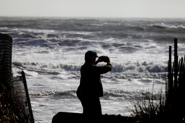 A man takes pictures with his phone at Higgins Beach in Scarborough on Tuesday, Oct. 30, 2012, the day after Hurricane Sandy.