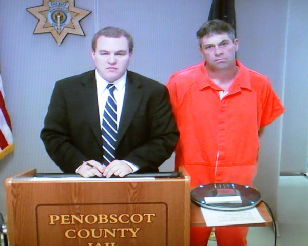 Jeffrey Macy, 46, (right) during his first appearance via video conference at the Penobscot Judicial Center in Bangor. On the left is Ben Fowler, his attorney for the day.