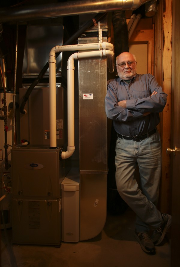 Allan Hoffman stands with his new high-efficiency furnace that will meet new federal standards coming next May, in the basement of his Coon Rapids, Minnesota home, Oct. 3, 2012. An indication of the new style furnace is the pair of PVC pipes that bring fresh, outside air directly into the furnace.