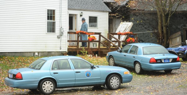 Maine State Police Trooper Christopher Cookson talks with a homeowner on Bowden Road in Corinna while investigating reports that the driver of a garbage truck was shot at on Tuesday, Oct. 30, 2012.