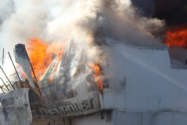 The Chevrolet sign collapses during a fire at Valley Auto in Fort Kent on Wednesday, Oct. 3, 2012.