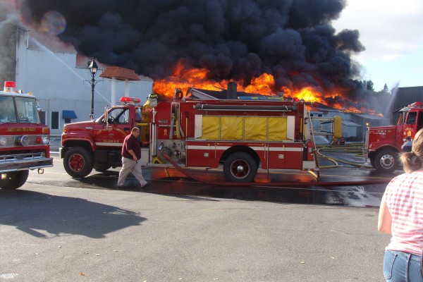 Firefighters, trucks and equipment from the fire departments of surrounding communities and both sides of the border tackle the blaze at Valley Auto in Fort Kent on Wednesday, Oct. 3, 2012.