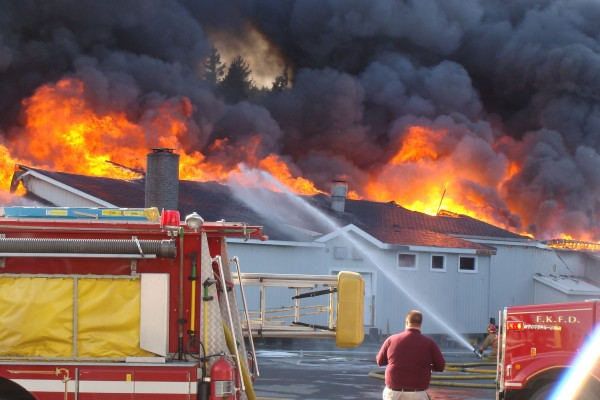 Flames shoot from the roof line as firefighters tackle a fire at Valley Auto in Fort Kent on Wednesday, Oct. 3, 2012.
