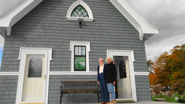 Joyce Fenner (left) and Ann Mullen pose in front of the recently restored chapel at Belfast's Grove Cemetery. The chapel will be open to the public 10 a.m. to 4 p.m. Friday, Oct 12, and cemetery tours will be offered at 10 a.m. and 1 p.m.