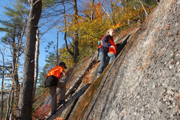Students from the William S. Cohen School Hiking Club use a ladder and rope to scale a steep portion of the trail leading up Woodchuck Hill in Eddington on Oct. 17, 2012.