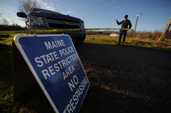 Lt. Jason Sattler of the Maine State Police motions to passersby as he stands guard at the end of Bobolink Drive in Lamoine around 5 p.m. Tuesday, Oct. 23, 2012. Maine State Police continued to investigate the scene there where two men were fatally shot early Tuesday morning.