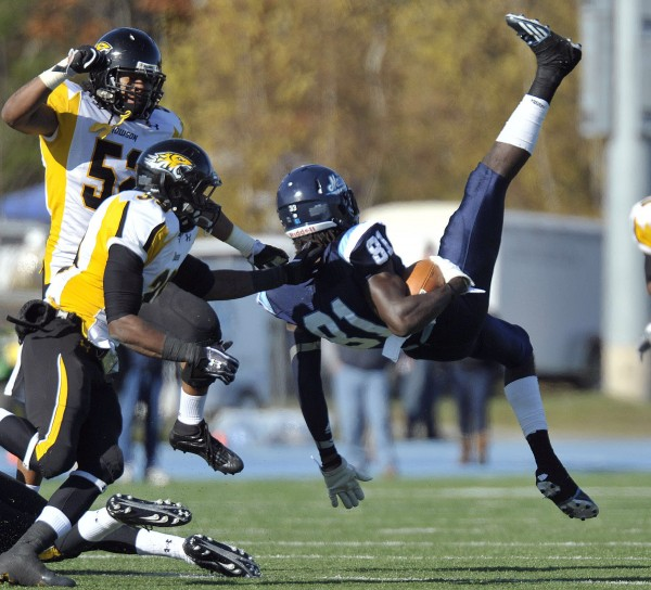 Towson's Denzel White (52) and Tye Smith (39) tackle Maine's Maurice McDonald (81) after a reception in the first half of an NCAA football game in Orono, Maine Saturday, Nov.5, 2011.