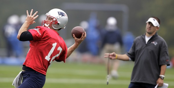 New England Patriots quarterback Tom Brady (12) throws a pass as offensive coordinator and quarterback coach Josh McDaniels looks on during practice at the NFL football team's facility in Foxborough, Mass., Wednesday, Oct. 3, 2012.