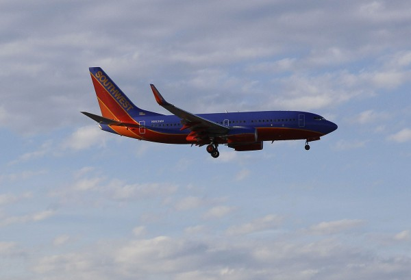 In this Thursday, March 22, 2012, file photo, a Southwest Airlines flight prepares to land at McCarran International Airport, in Las Vegas. Southwest Airlines eked out a small third-quarter profit in spite of a September slowdown, the company said on Thursday, Oct. 18, 2012.
