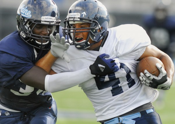 UMaine's Malik Walker (34) takes down teammate Nigel Jones (41) during a intrasquad scrimmage in August on Morse Field in Orono.