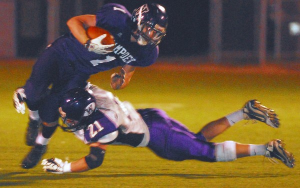 Hampden Academy's Benjamin Cambridge (left) is taken down by Waterville's Racean Wood (21) during second half action of playoff football at Hampden Academy Friday night Oct. 26 2012. Waterville knocked off Hampden 25-17.