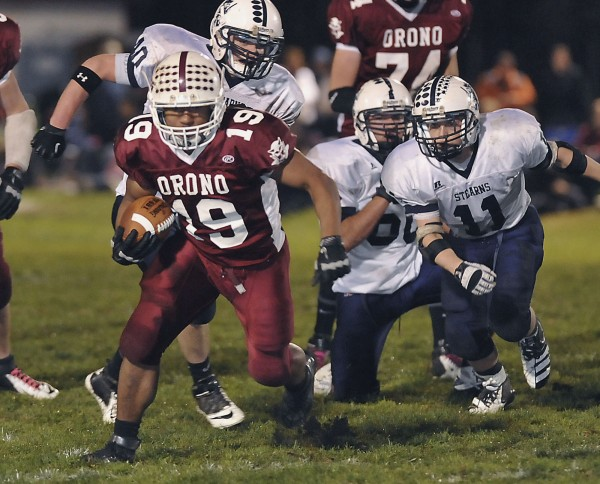 Orono High School halfback Norton Revell (19) breaks away from Stearns High School players Jordan Morrow (11) and Tyson Girsa (40) on a carry in the first half of their game in Orono, Maine, Friday, Oct. 26, 2012.