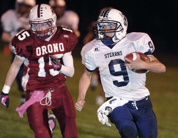 Stearns High School quarterback Mark Lyons (9) carries the ball under the pursuit of Orono safety Dennis Farnham (15) in the first half of their game in Orono, Maine, Friday, Oct. 26, 2012.