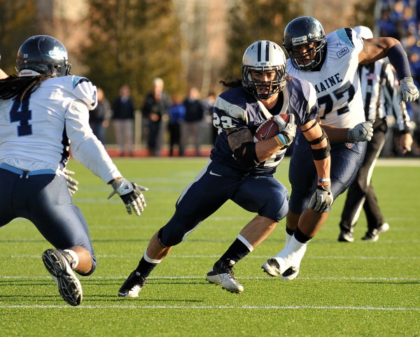 New Hampshire running back Nico Steriti (22) runs past Maine linebacker Vinson Givans (4) for a touchdown during last season's game at Cowell Stadium in Durham, N.H. UNH beat Maine 30-27. The two teams will meet for the 100th time at noon Saturday at Alfond Stadium in Orono.