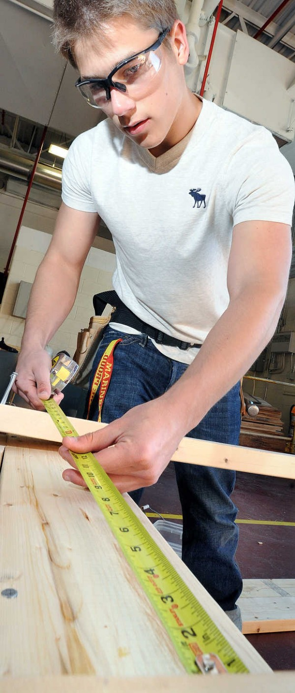 Lewiston Regional Technical Center student Tyler Ford measures wood that will be used to construct a bench for a chop saw in his carpentry/building construction program.