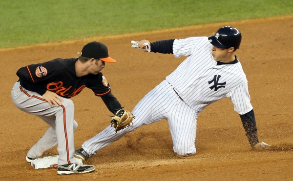 Oct 12, 2012; Bronx, NY, USA;  New York Yankees first baseman Mark Teixeira (right) steals second base as Baltimore Orioles shortstop J.J. Hardy (left) is late with the tag during the fifth inning of game five of the 2012 ALDS at Yankee Stadium.