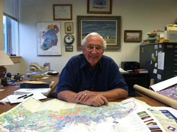 Geologist Harold Borns in his office at the University of Maine. In front of him on his desk sits one of his proudest accomplishments: Maine's Ice Age Trail, Downeast ecotourism trail map.