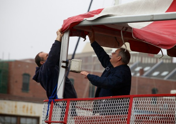 Lloyd Jones (left) and Bruce Woodman remove an awning from a ferry boat at the Casco Bay Lines terminal in Portland Monday morning Oct. 29, 2012, ahead of Hurricane Sandy.