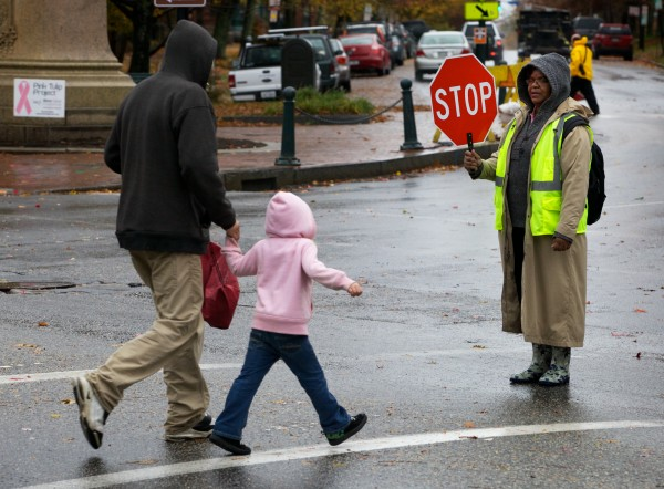 A crossing guard who didn't want to give her name stops traffic for pedestrians on their way to school Monday morning Oct. 29, 2012, in Portland's Longfellow Square. City schools are getting out am hour early today and all after school activities have been canceled ahead of Hurricane Sandy.