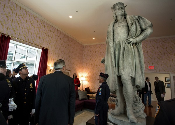 An NYPD officer looks up to a statue of Christopher Columbus as leaders of the Italian-American community, civil servants from New York and Italy, including police and sanitation workers and other guests, stand in what is known as the living room created by artist Tatzu Nishi that surrounds Gaetano Russo's 1892 sculpture of Christopher Columbus 75 feet above Columbus Circle Sunday, Oct. 7, 2012, in New York.
