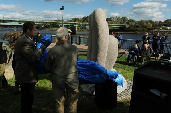 Bangor City Council Chairman Cary Weston (left) and John Rohman unveil a granite sculpture along the Bangor Waterfront on Thursday, Oct. 11, 2012. Artisit Koichi Ogino of Japan was selected from a group of eight that participated in the Schoodic International Sculpture Symposium to create the piece for Bangor.