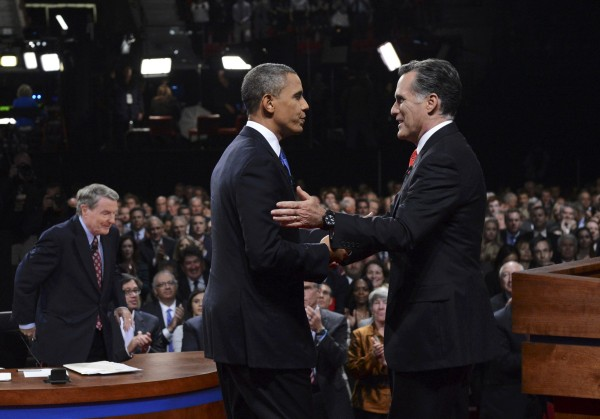 Republican presidential nominee Mitt Romney shakes hands with President Barack Obama as mediator Jim Lahrer gets up at the end of the first 2012 U.S. presidential debate in Denver October 3, 2012.