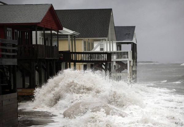 A wave crashes over the protecting sandbags in front of the houses on the east side of Ocean Isle Beach during Hurricane Sandy in Ocean Isle Beach, North Carolina, Oct. 27.
