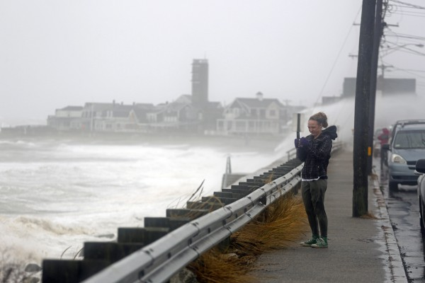 Oct 29, 2012; Ocean Bluff, MA, USA; A woman stops to take a photo of the waves of Hurricane Sandy as they crash along the seawall of Route 139.